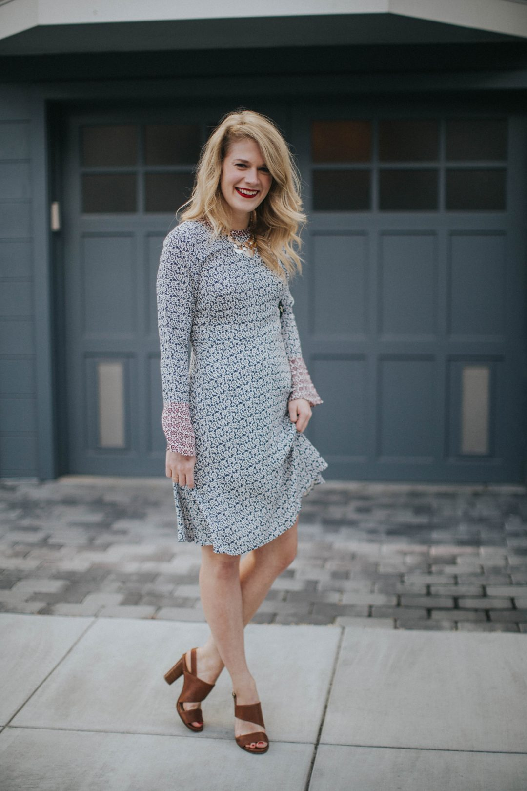 Blogger Cait Weingartner of Pretty & Fun wearing a LOFT floral bell sleeve dress with M. Gemi sandals and a BaubleBar statement necklace.